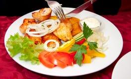 Bistecca cotta del pollo, patate cotte e verdure con il coltello una forcella Immagine Stock