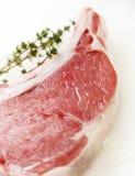 Bistecca cruda con timo su un tagliere bianco Immagini Stock