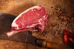 Bistecca cruda della carne del manzo sulla tavola di legno con la mannaia di carne fotografia stock libera da diritti