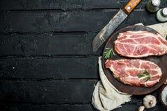 Bistecca cruda della carne di maiale con un vecchio coltello su un tagliere fotografie stock libere da diritti