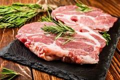 Bistecca cruda della carne di maiale su un bordo di legno Immagini Stock