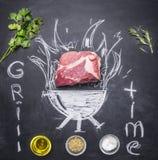 Bistecca cruda della carne di maiale su una lavagna dipinta con una griglia bruciante con le erbe e spezie, petrolio ed iscrizion Fotografia Stock Libera da Diritti