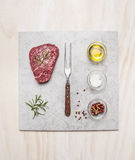 Bistecca cruda della carne fresca con gli ingredienti della spezia sul piatto di marmo leggero sopra fondo di legno, vista superi immagini stock