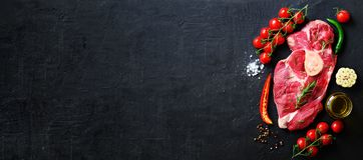 Bistecca cruda della carne fresca con i pomodori ciliegia, il peperoncino, l'aglio, il petrolio e le erbe sulla pietra scura, fon Fotografia Stock