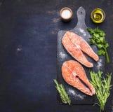 Bistecca cruda due al salmone, frutti di mare, alimento sano con il tagliere d'annata scuro delle erbe, del prezzemolo, dell'olio Fotografia Stock Libera da Diritti