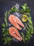 Bistecca cruda due al salmone, frutti di mare, alimento sano con il tagliere d'annata scuro delle erbe, del prezzemolo, dell'olio Fotografie Stock Libere da Diritti