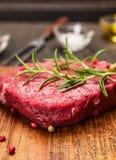 Bistecca cruda su un tagliere con una forcella, i rosmarini, un sale e un olio su fondo di legno rustico, fine su fotografia stock