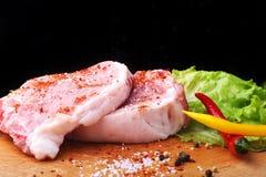 Bistecca cruda, taglio su un tagliere rustico con sale, pepe e smerigliatrice per le spezie Fondo nero per lo spazio della copia fotografie stock libere da diritti