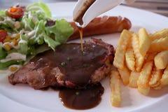 Bistecca della carne di maiale con salsa e le patate fritte sul piatto Fotografie Stock Libere da Diritti