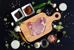 Bistecca della carne su un tagliere e su un pepe, foglia di alloro, rosmarino, cipolle, sale, olio d'oliva, salsa di soia Immagine Stock