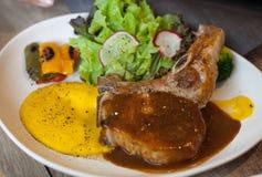 Bistecca di braciola di maiale con salsa ed il piatto laterale Fotografia Stock