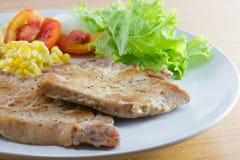Bistecca di braciole di maiale con insalata e francese fritti Fotografia Stock