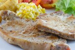Bistecca di braciole di maiale con insalata e francese fritti Fotografie Stock