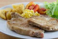 Bistecca di braciole di maiale con insalata e francese fritti Immagine Stock Libera da Diritti