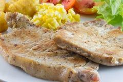 Bistecca di braciole di maiale con insalata e francese fritti Fotografie Stock Libere da Diritti