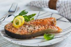 Bistecca di color salmone arrostita con il limone e le erbe fotografie stock