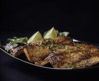 Bistecca di color salmone caramellata su fondo nero Fotografia Stock