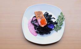 Bistecca di color salmone con la salsa crema della barbabietola della pasta dell'inchiostro del calamaro che frigge tobiko uovo d Fotografia Stock