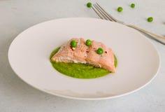 Bistecca di color salmone cotta con i semi di sesamo e servita con i piselli schiacciati fotografie stock