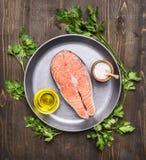Bistecca di color salmone cruda con le erbe, il prezzemolo, l'olio d'oliva ed il sale su una fine rustica di legno di vista super Fotografie Stock