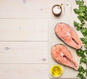 Bistecca di color salmone cruda della preparazione di concetto con le erbe, il prezzemolo, l'olio d'oliva ed il sale sul fondo ru Fotografia Stock