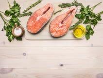 Bistecca di color salmone cruda della preparazione di concetto con le erbe, il prezzemolo, l'olio d'oliva ed il sale sul fondo ru Fotografie Stock