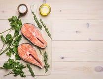 Bistecca di color salmone cruda della preparazione di concetto con le erbe, il prezzemolo, l'olio d'oliva ed il sale sul fondo ru Immagine Stock Libera da Diritti