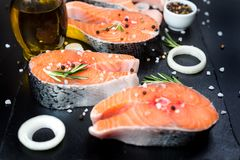 Bistecca di color salmone cruda sulla pietra nera, per cucinare Fotografia Stock