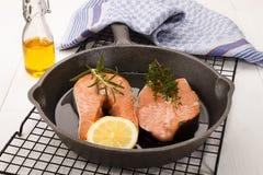 Bistecca di color salmone cruda in una pentola del ghisa Fotografia Stock