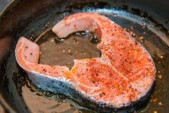 Bistecca di color salmone nella padella fotografie stock libere da diritti