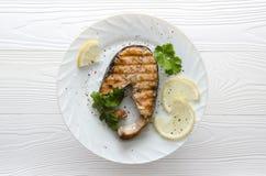 Bistecca di color salmone sul piatto bianco su fondo di legno bianco Immagine Stock