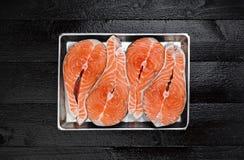 Bistecca di color salmone sul vassoio del metallo sulla vista di legno nera del piano d'appoggio Immagine Stock Libera da Diritti
