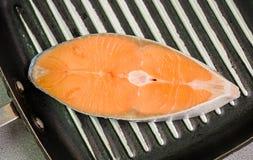Bistecca di color salmone sulla pentola fotografia stock