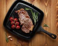 Bistecca di controfiletto con i rosmarini ed i pomodori ciliegia sulla padella Immagine Stock