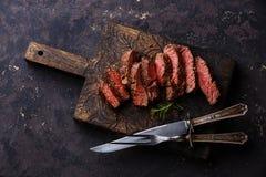 Bistecca di manzo arrostita affettata con il coltello e la forcella fotografie stock libere da diritti