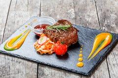 Bistecca di manzo arrostita con insalata fresca e la salsa del bbq sul fondo di pietra dell'ardesia sulla fine di legno del fondo Immagine Stock