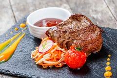 Bistecca di manzo arrostita con insalata fresca e la salsa del bbq sul fondo di pietra dell'ardesia sulla fine di legno del fondo Fotografie Stock