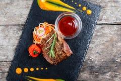 Bistecca di manzo arrostita con insalata fresca e la salsa del bbq sul fondo di pietra dell'ardesia sulla fine di legno del fondo Fotografia Stock Libera da Diritti