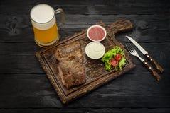Bistecca di manzo arrostita con le salse e la tazza di birra su un bordo Tavola di legno scura Fotografie Stock