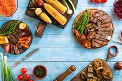 Bistecca di manzo arrostita con le verdure arrostite sulla tavola blu di legno Immagini Stock Libere da Diritti