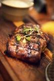 Bistecca di manzo arrostita succosa su un piatto di legno Fotografia Stock