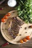 Bistecca di manzo arrostita sul bordo di legno su fondo di legno Fotografia Stock Libera da Diritti