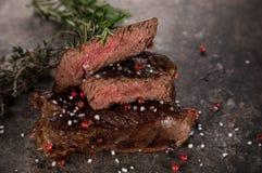 Bistecca di manzo arrostita sulla tavola di pietra nera immagine stock libera da diritti