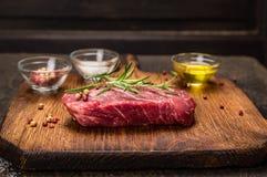 Bistecca di manzo con gli ingredienti per la cottura - rosmarini, petrolio e spezie sul tagliere rustico sopra fondo di legno scu fotografie stock libere da diritti