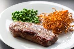 Bistecca di manzo con i piselli e la patata dolce Fotografia Stock Libera da Diritti