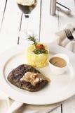 Bistecca di manzo con la patata di poltiglia ed il vino bianco su un fondo bianco Immagine Stock Libera da Diritti