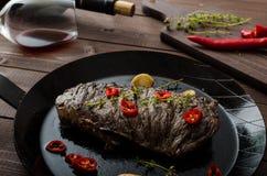 Bistecca di manzo con le erbe ed i peperoncini rossi, foto del prodotto Immagini Stock
