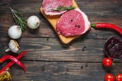 Bistecca di manzo cruda con i pomodori ed il fondo scuro della tavola di chillion del pepe, vista superiore Copyspace Fotografia Stock Libera da Diritti