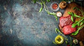 Bistecca di manzo cruda ed ingredienti freschi per la cottura sul fondo rustico, vista superiore, insegna