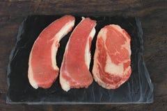Bistecca di manzo cruda su fondo, sulla carne dell'alimento o sul barbecue scura di legno fotografie stock libere da diritti
